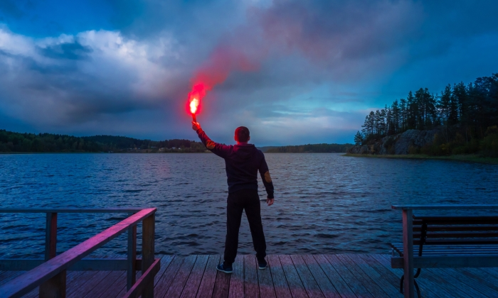 Man holding flare on water's edge